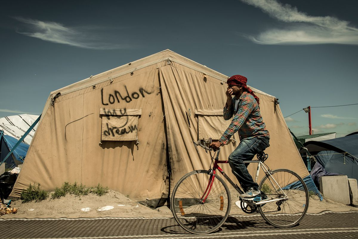 A boy rides his bicycle past a tent in the Calais migrant camp.