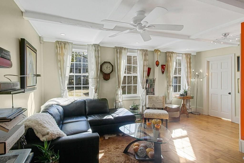 A living room with a low ceiling, three windows, a sectional couch, and a ceiling fan.