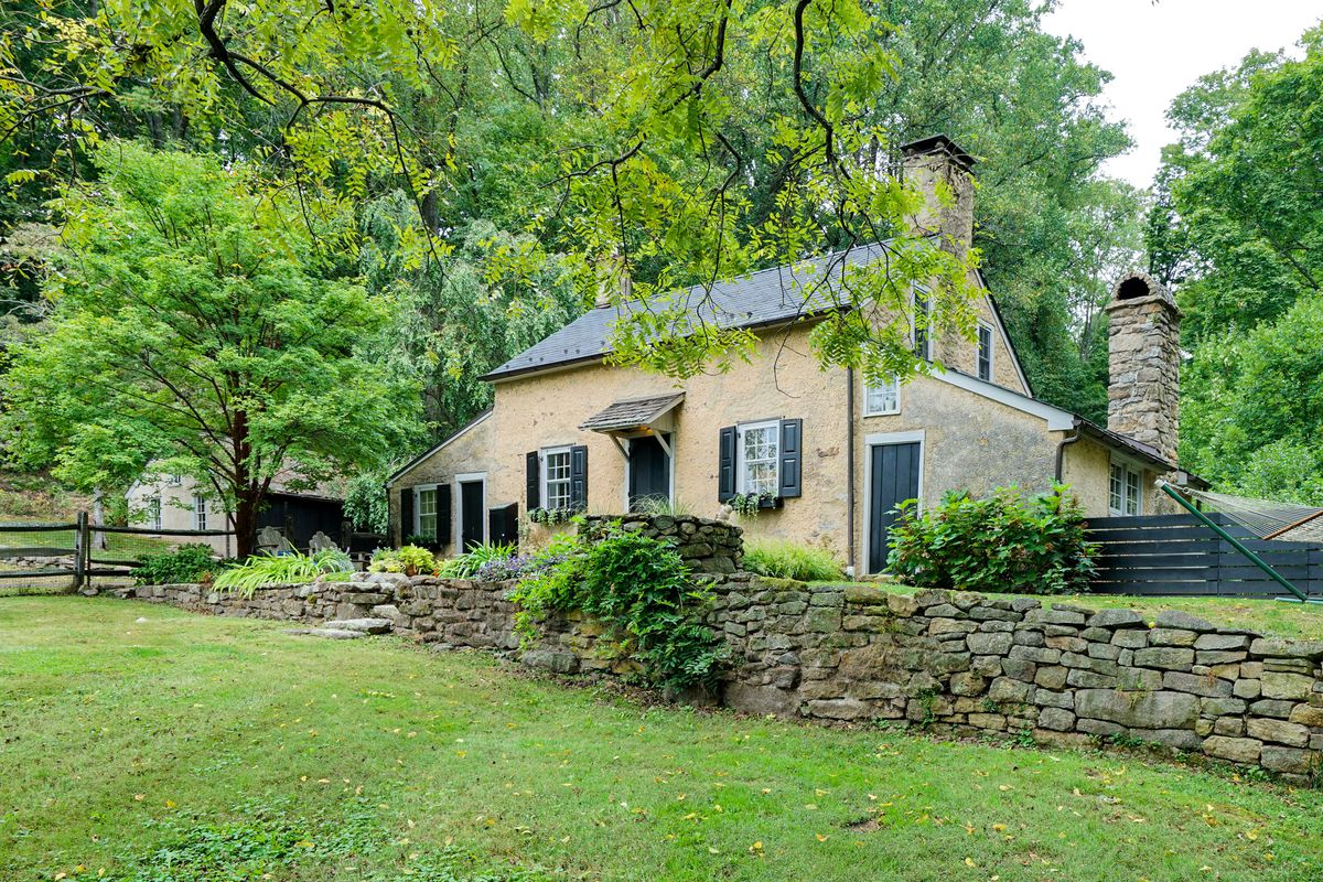 A small cottage surrounded by trees and old stone walls.