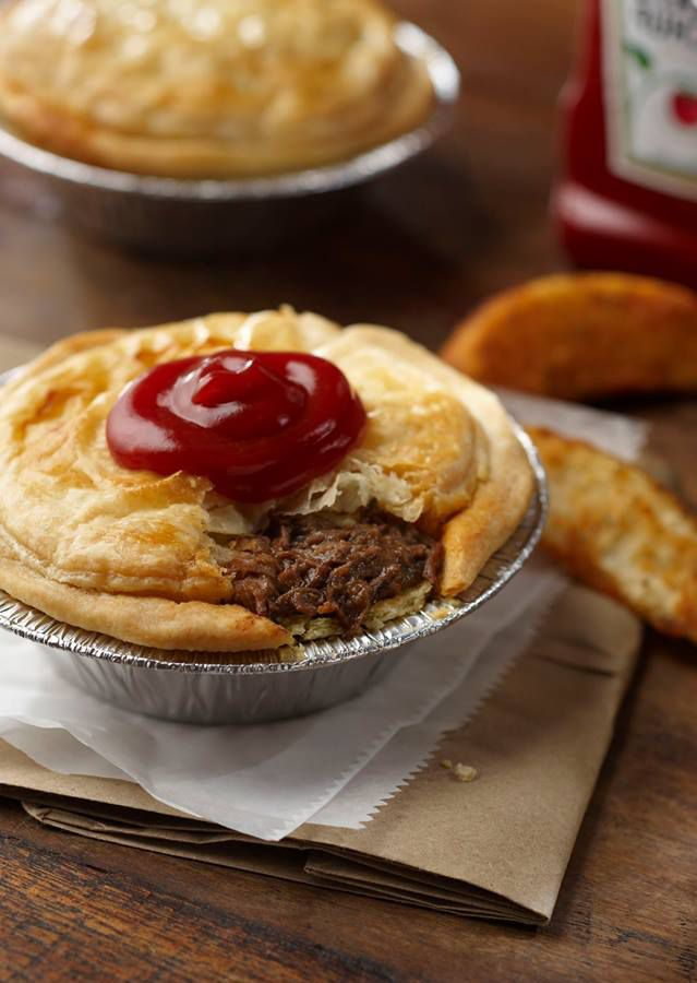 A flaky Australian meat pie with a bite taken out of it is garnished with a large dollop of ketchup