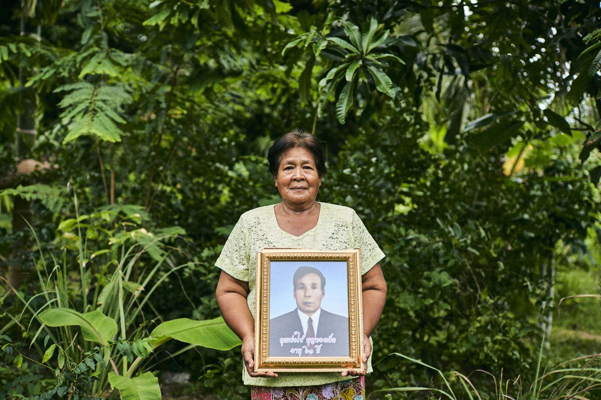 A woman stands with a portrait of a man