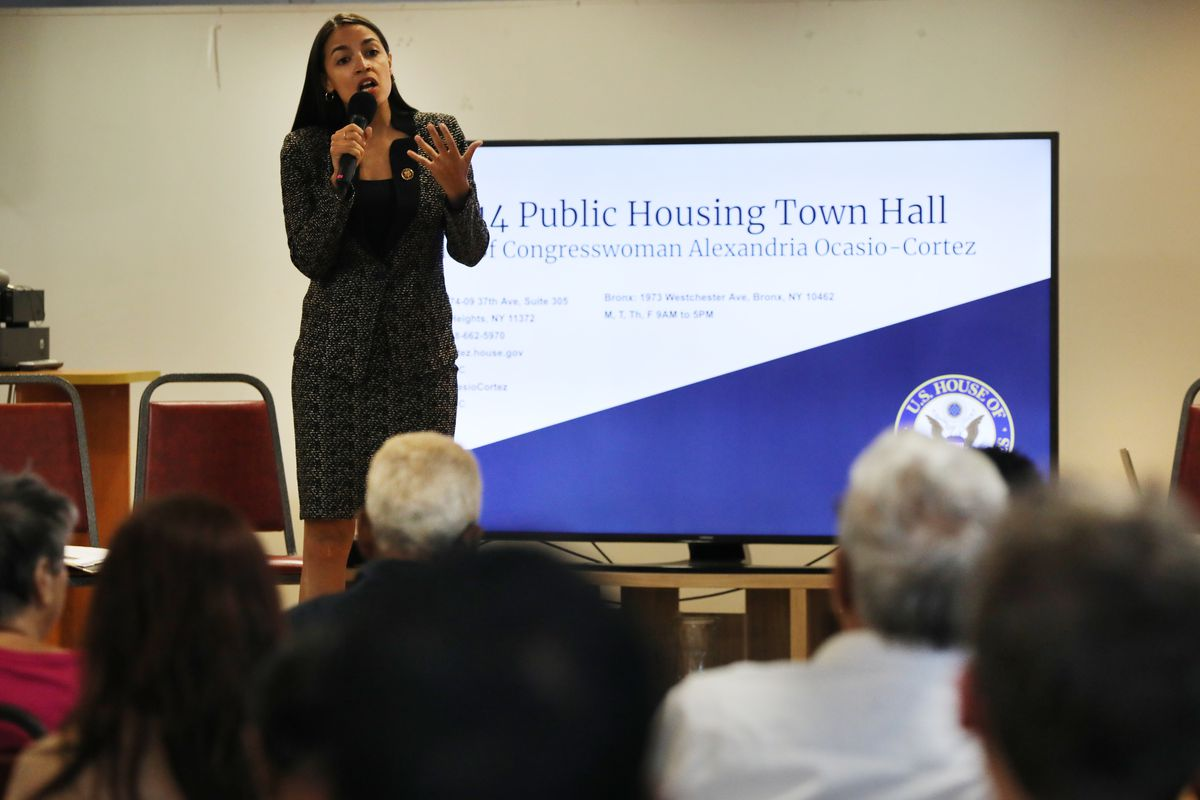 Representative Alexandria Ocasio-Cortez on stage, speaking to constituents in the Bronx at a public meeting.