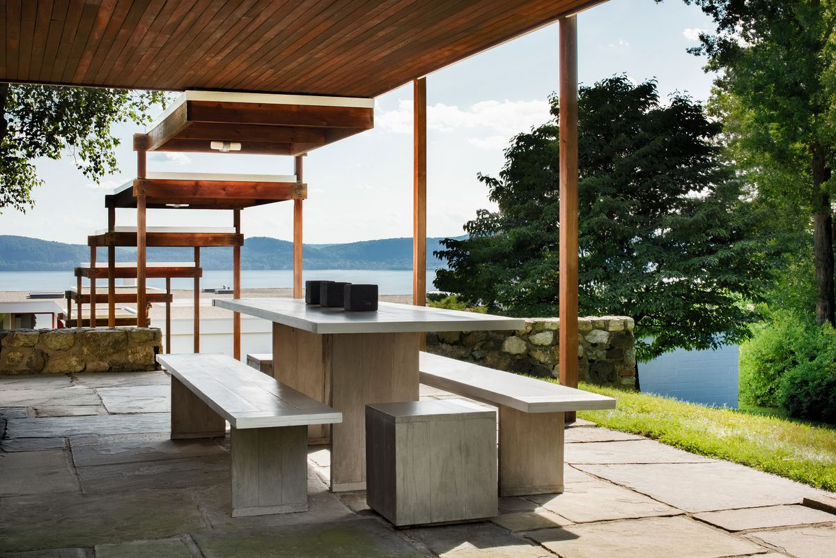 A concrete picnic table sits under a covered patio outside.