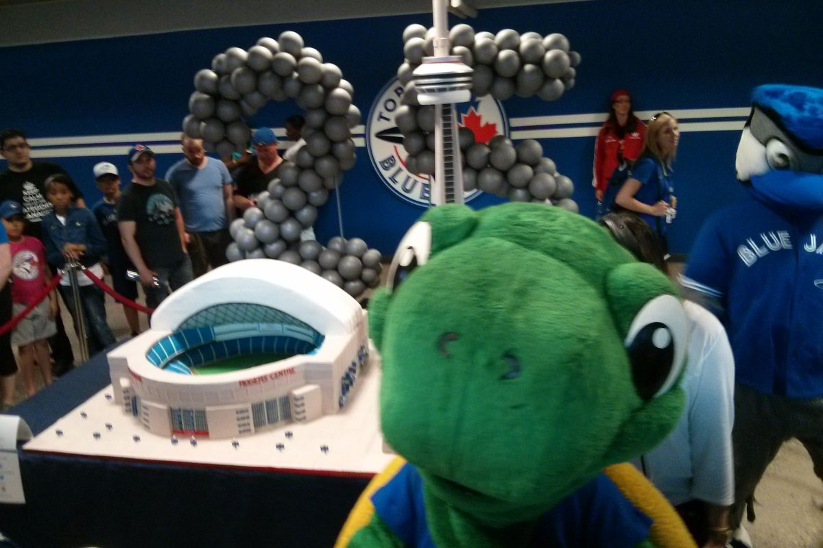 Domer photobombing a picture of the Rogers Centre-CN Tower cake.