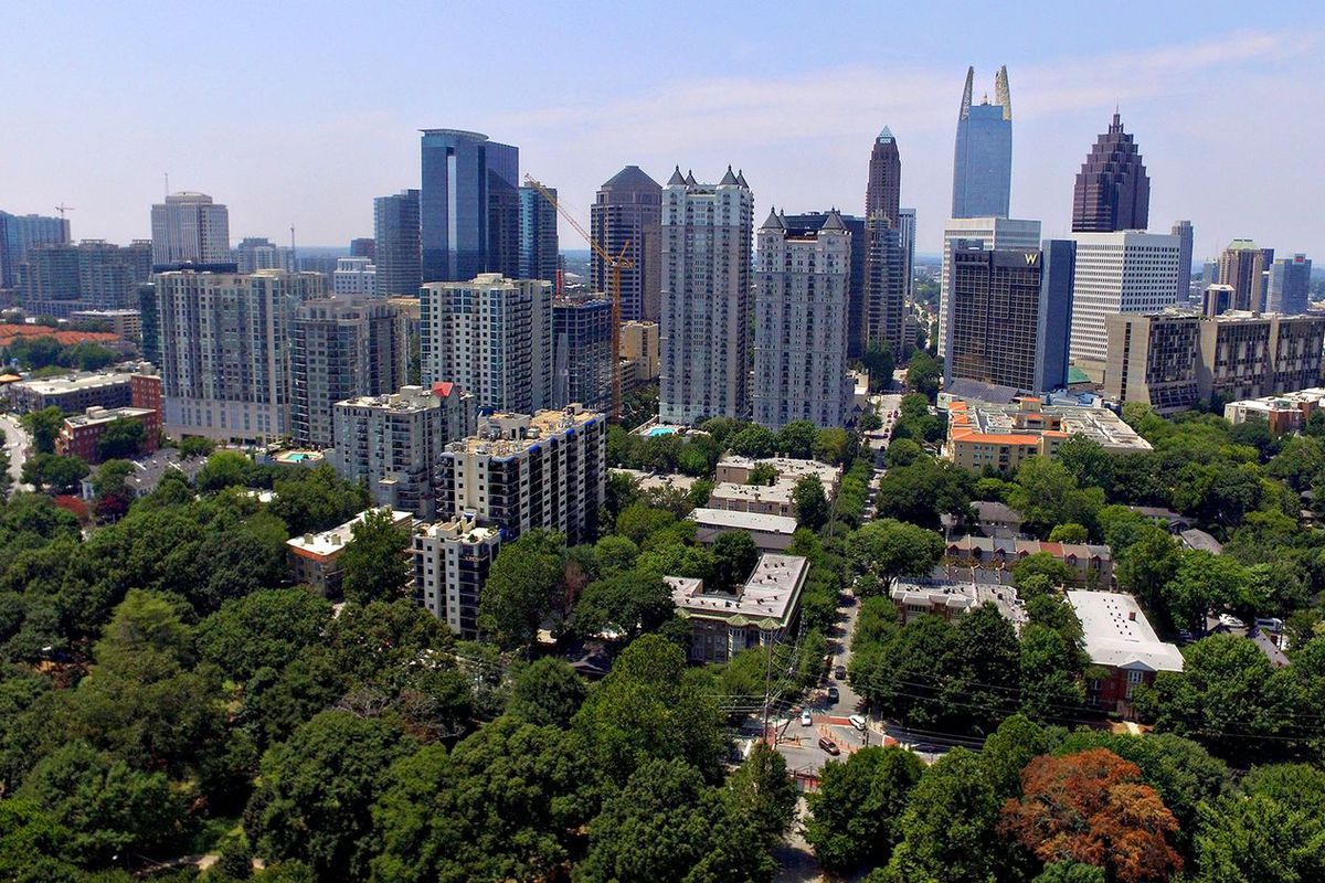An aerial view of large glassy and steel buildings in Atlanta with trees and smaller buildings at left.
