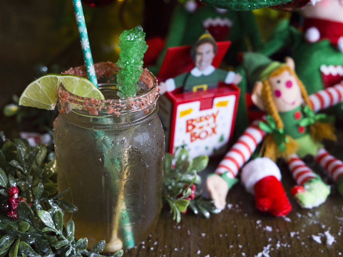 A cocktail in mason jar with a Will Ferrell elf and other toys around it.
