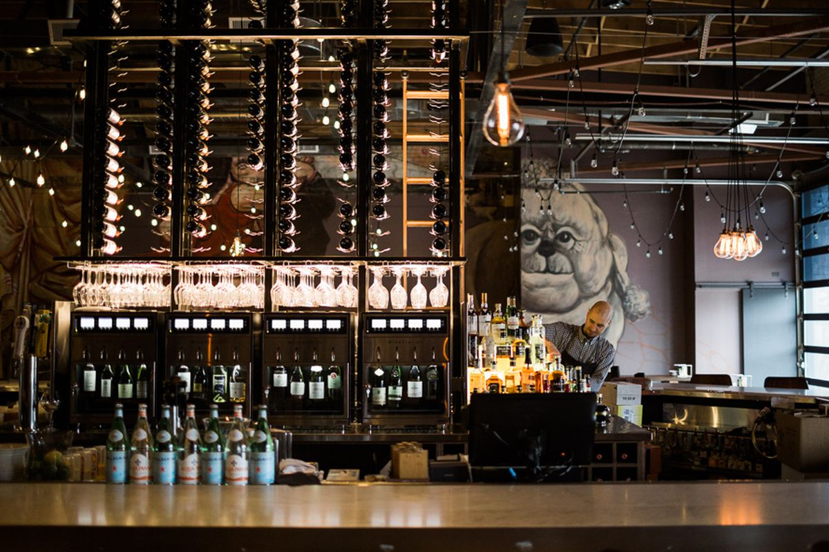 A large metal wine rack hangs behind the bar counter at the center of the dining room inside Pop's for Italian in Ferndale.