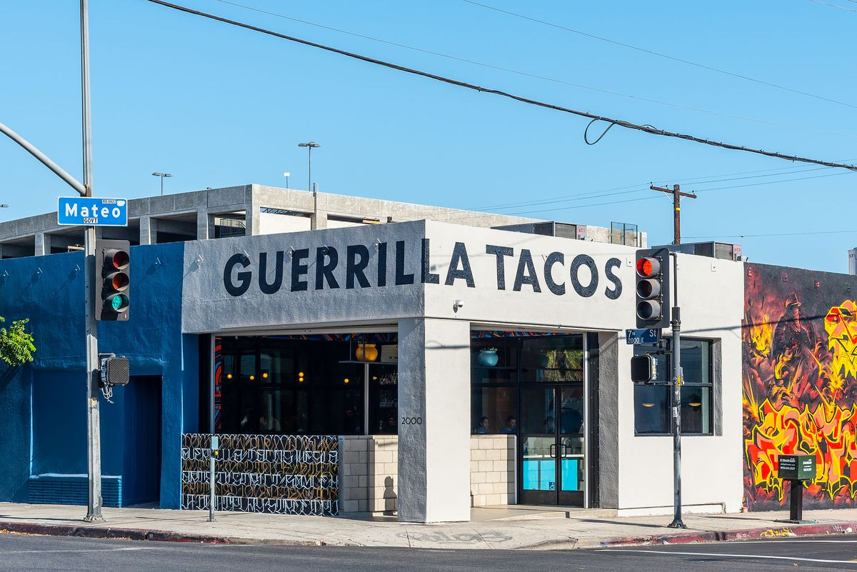 Signage for Guerrilla Tacos, a white painted wraparound corner building.