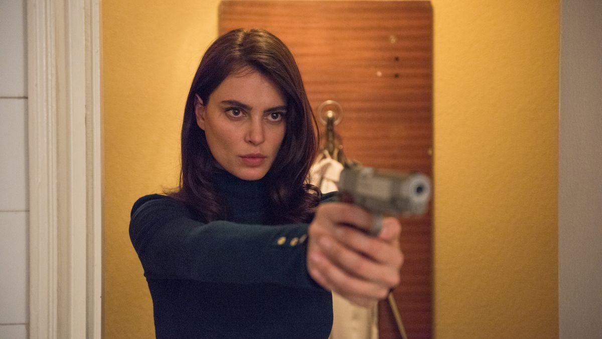 A woman points a gun.