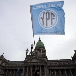 """A supporters of an oil nationalization bill proposed by Argentina's President Cristina Fernandez holds a flag reading in Spanish """"Fight and return YPF"""" outside Congress as senators debate the bill in Buenos Aires, Argentina, Wednesday, April 25, 2012. Fernandez, who pushed forward a bill to renationalize the country's largest oil company, said the legislation put to congress would give Argentina a majority stake in oil and gas company YPF by taking control of 51 percent of its shares currently held by Spain's Repsol."""