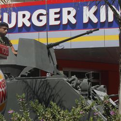 A Lebanese army soldier sits on his armored personnel carrier, as he stands guard outside the Burger King as part of stepped up security measures, in the southern port city of Sidon, Lebanon, Saturday Sept. 15, 2012. Security forces in Lebanon beefed up security presence around U.S. fast food restaurants Saturday, a day after a crowd angry over the anti-Islam movie set fire to a KFC and a Hardee's restaurant in Tripoli north of Lebanon, sparking clashes with police. At least one of the attackers was killed and 25 people wounded in the melee.