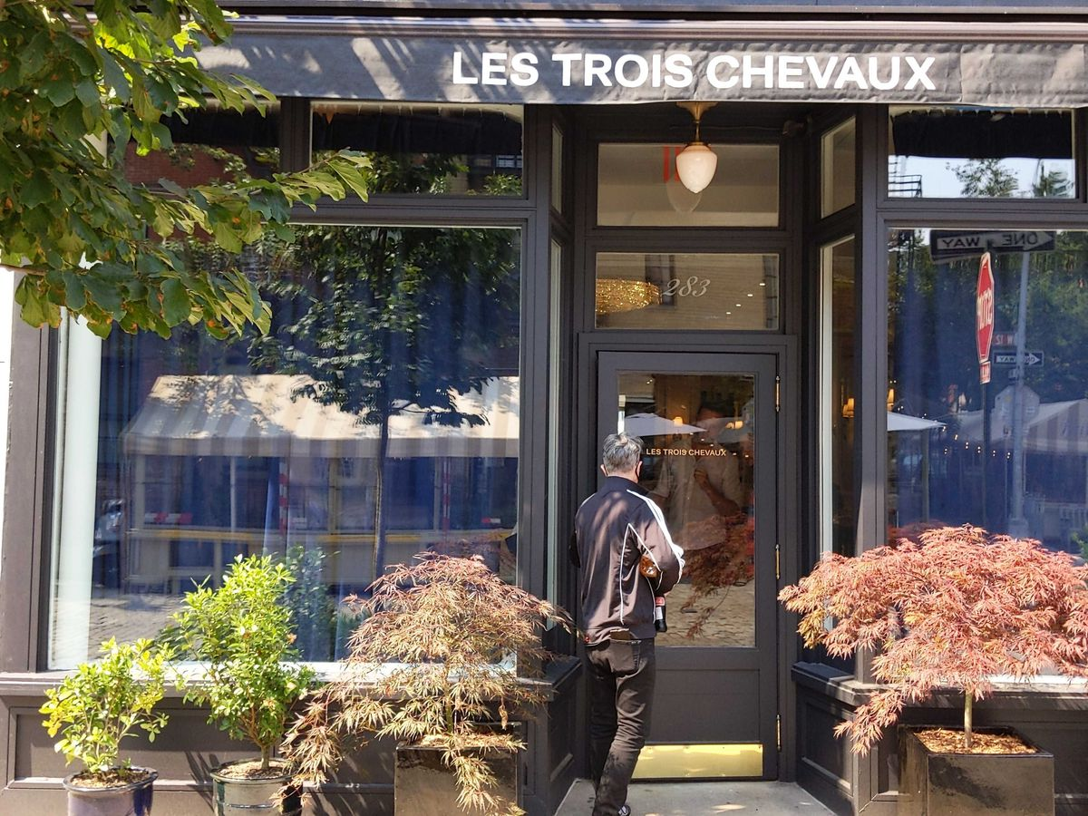 """A person opens the door to a restaurant with plants and trees out front and an awning that reads """"Les Trois Chevaux"""""""