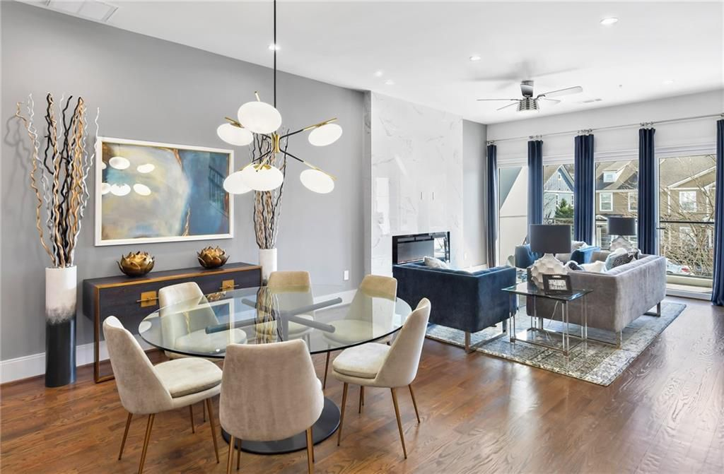 A gray and white dining and living room with blue furniture.