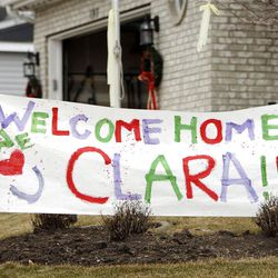 """Neighbors Jeremy and Ali Jackson hang a """"welcome home"""" sign in the yard of Clara Lewis prior to her return from the hospital on Thursday."""