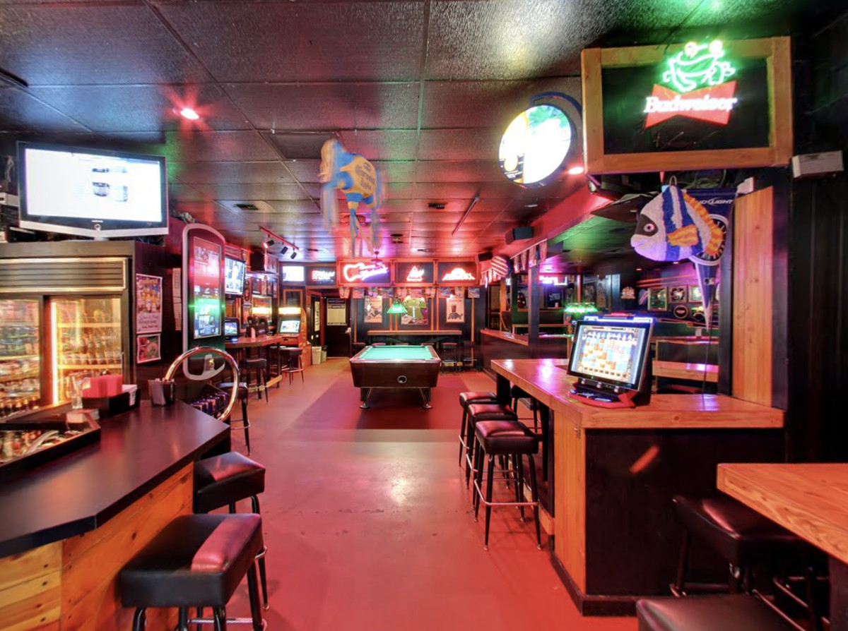 An interior look at Madison Pub, with a pool table in the middle, TVs, and glowing neon signs.