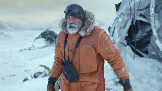 A bearded George Clooney walks out into the snowy tundra with an orange parka in The Midnight Sky