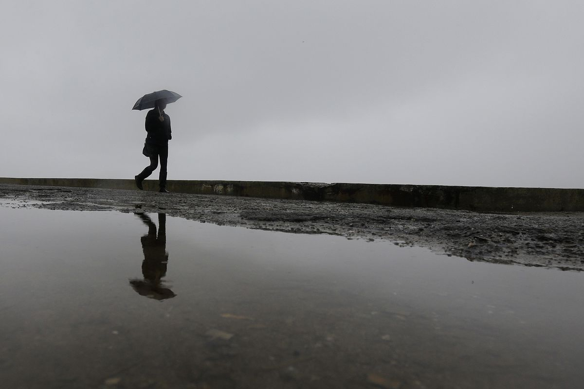 A woman walks past a puddle on a pier at Fort Point in San Francisco on Monday.