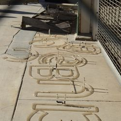 1:49 p.m. Another view of the neon letters, laid out on the ground in front of Gate F -