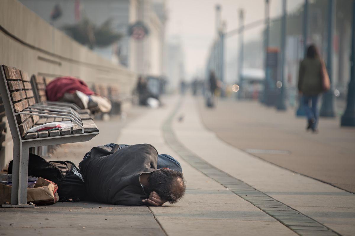 A homeless man sleeps under a bench.