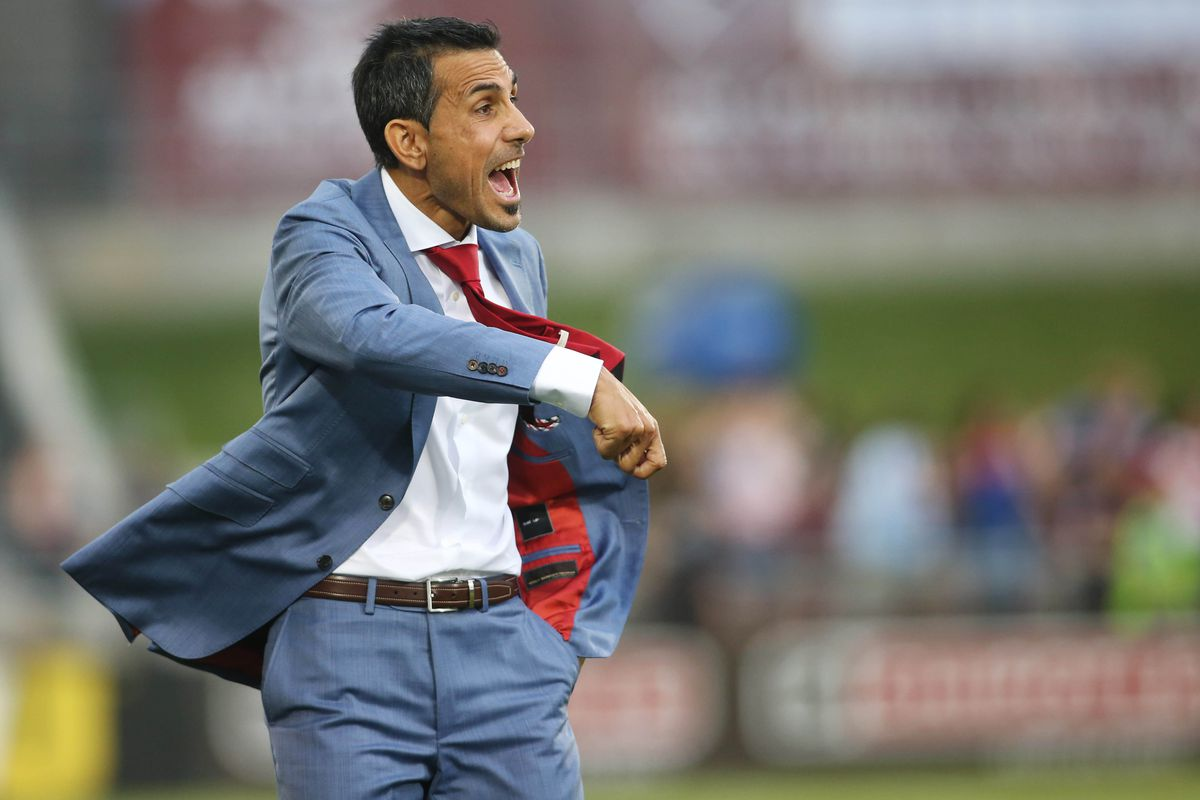 Pablo Mastroeni, in a dapper blue suit, giving instructions from the touchline.