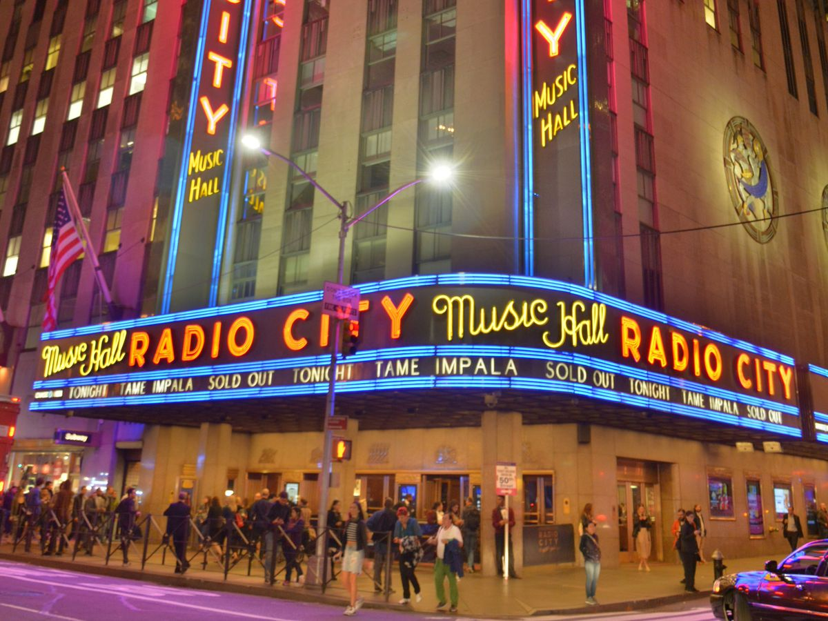 The exterior of a concert hall. There is a neon sign that reads Radio City Music Hall. There are people standing outside of the concert hall.