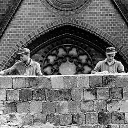 Two East German workers working on a huge 15 feet hight Wall put pieces of broken glass on the top to prevent East Berliners from escaping.