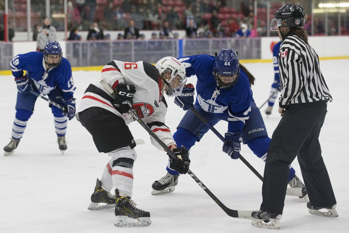 Jenna Dingeldein(44) of the Toronto Furies faces off against Brooke Webster(26) of the Vanke Rays. An official stands ready to drop the puck and Furies forward Brittany Zuback (19) waits in the background.