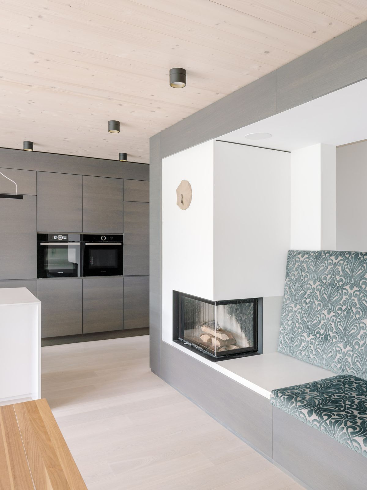 A glass fireplace is embedded in a white wall. Gray kitchen cabinets are in the background.