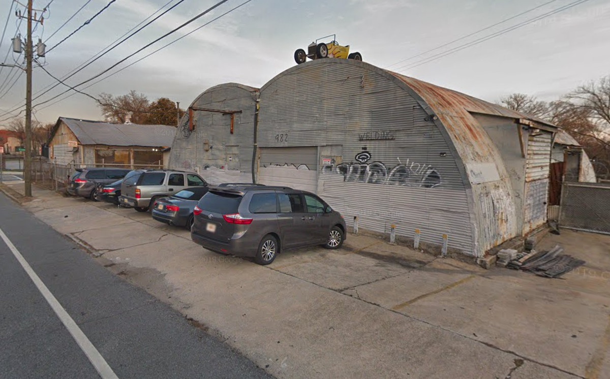 A rusting metal hangar with cars parked out front.