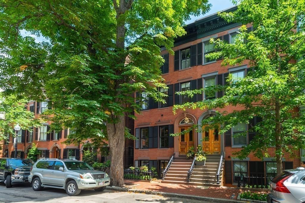 The exterior of a four-story townhouse on a sidewalk with trees in front of the house.