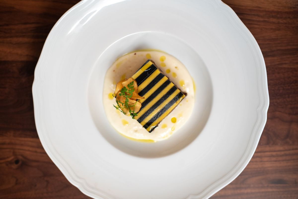 A checkered black and yellow square dish placed in a sauce on a white plate