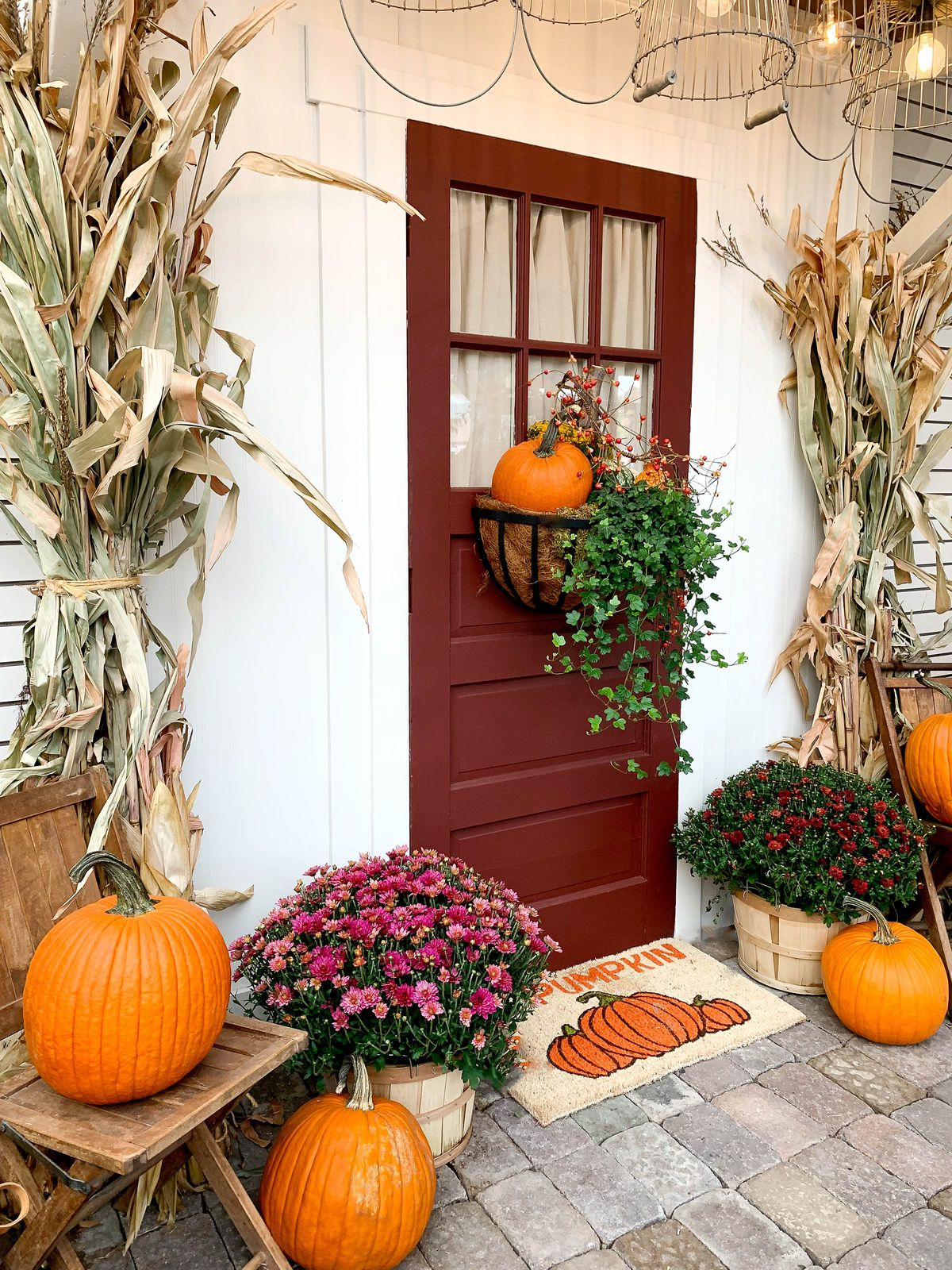 A front door with fall decor including mums in apple crates, pumpkins and dried corn stalks.