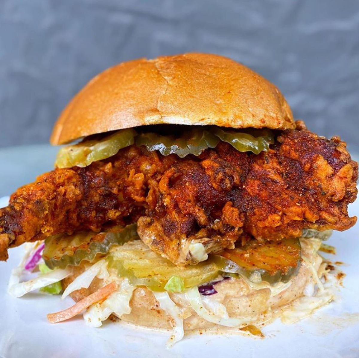 A seriously spiced, crispy fried chicken breast dominates a buttery bun with pickle rounds on the top and bottom with a layer of slaw on the bottom. Juices are dripping off the sandwich and pooling on the plate.