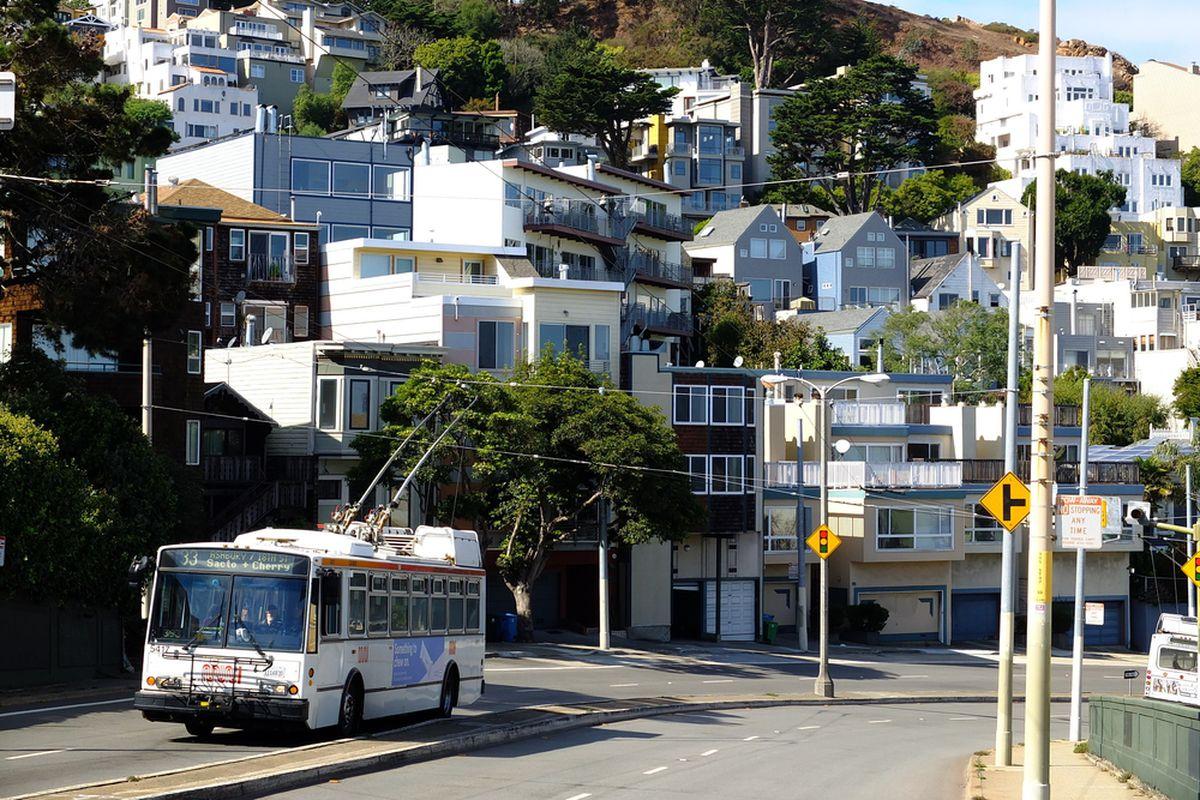 A Muni bus driving past hillside SF houses.