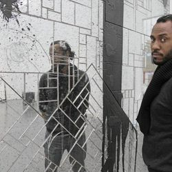 In this photo taken, Friday, April 6, 2012, artist Rashid Johnson poses with some of his work that is part of his first solo exhibition at the Museum of Contemporary Art in Chicago. In the last year, the Chicago native whose works made from everyday objects explore his own life story as well as larger issues of black identity, has garnered high-profile attention and awards from the art world.