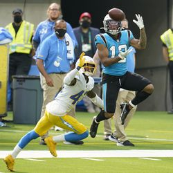 Carolina Panthers wide receiver D.J. Moore (12) makes a catch in front of Los Angeles Chargers cornerback Michael Davis during the second half of an NFL football game Sunday, Sept. 27, 2020, in Inglewood, Calif.