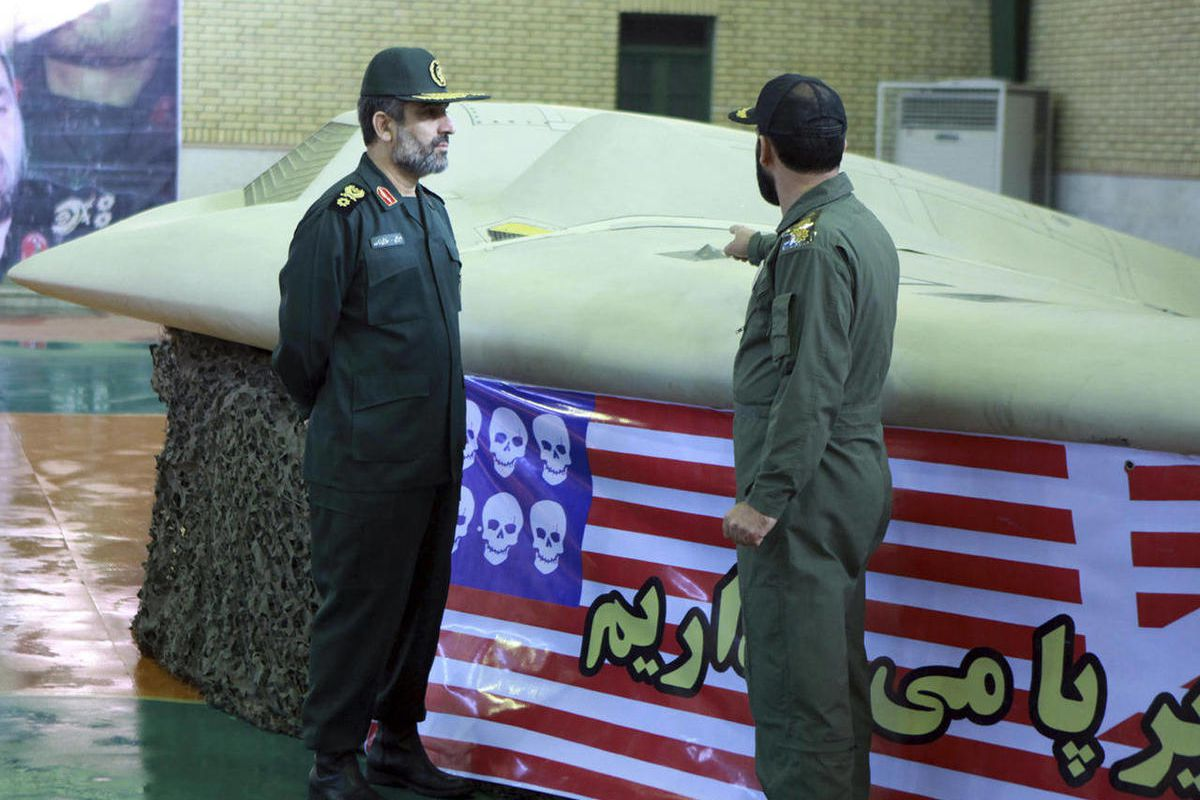 FILE - This photo released on Thursday, Dec. 8, 2011 by the Iranian Revolutionary Guards, claims to show the chief of the aerospace division of Iran's Revolutionary Guards, Gen. Amir Ali Hajizadeh, left, listening to an unidentified colonel pointing to a