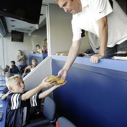 Former BYU Cougar basketball player Travis Hansen hands his son Mason some snacks during a BYU football game in Provo  Friday, Sept. 23, 2011.  Hansen is retiring from professional basketball.