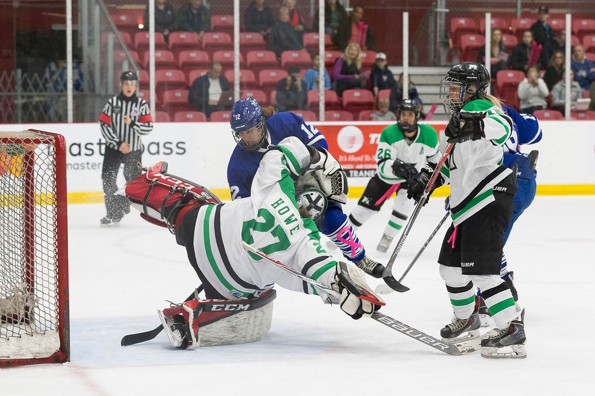 Markham Thunder goalie Erica Howe stops a shot by Toronto Furies Jessie Vella, supported by several other Thunder players.
