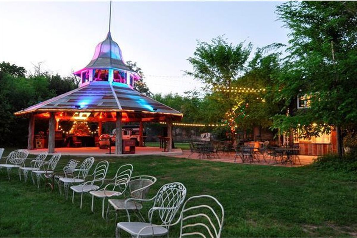 A big pavilion with cupola surrounded by trees and twinkly lights and chairs