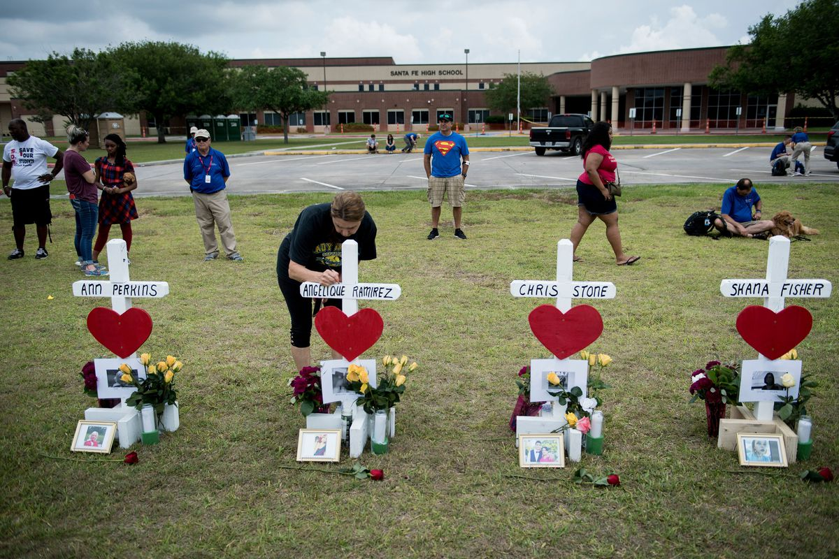 People pay their respects to victims of the Santa Fe High School shooting victims.