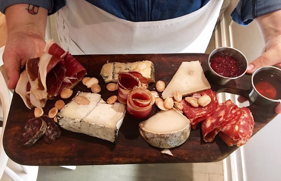 A wooden board full of various cheese and sliced charcuterie at Epicerie