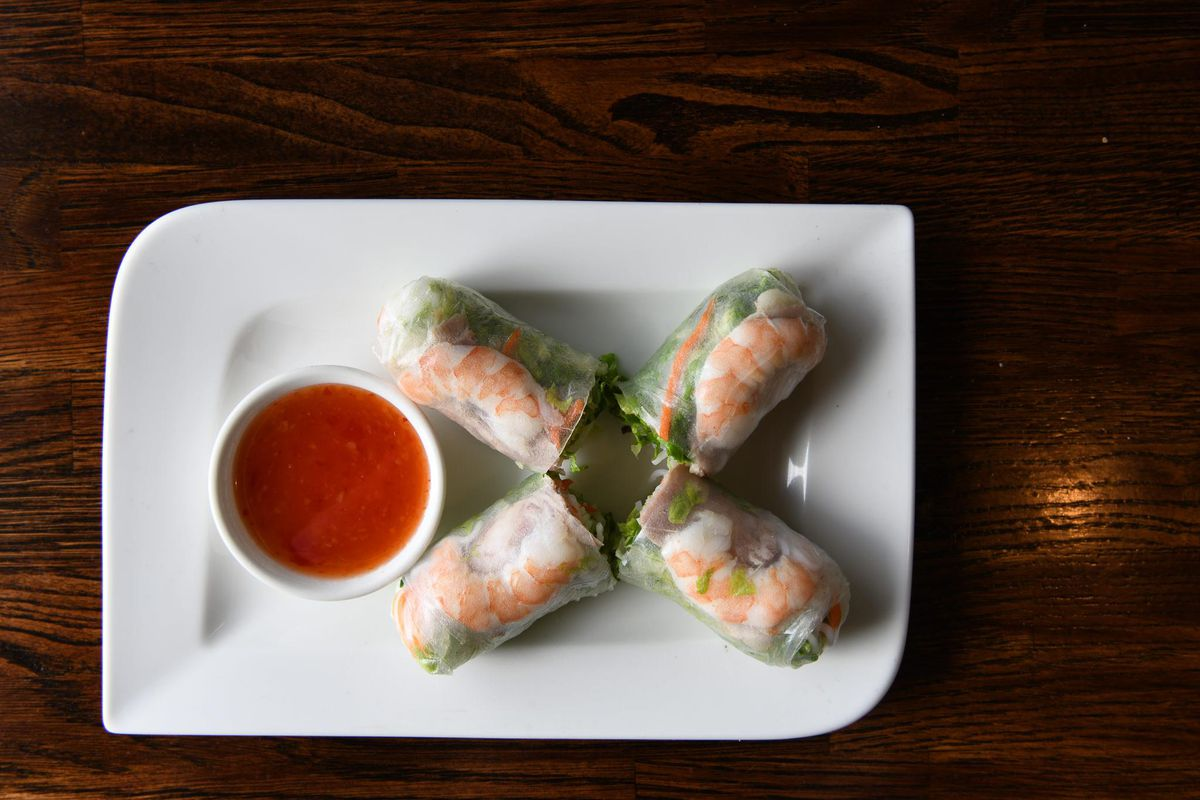 A white plate with four spring rolls and a ramekin filled with sauce