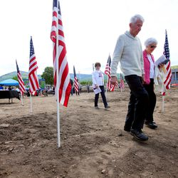 People walk past American flags as they leave a groundbreaking ceremony for the Bountiful Veterans Park in Bountiful on Tuesday, May 26, 2020.