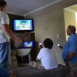 The Patient Empowerment Interactive Video Game was developed by professors and graduate students at the University of Utah. The project was inspired by 8-year-old Charlie, who has been diagnosed with a brain tumor. Charlie is pictured here playing the game at his home with student developers and his family.
