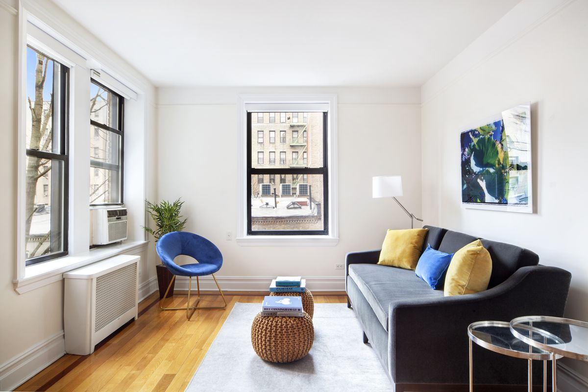A living area with hardwood floors, three windows, a couch, a grey rug, a planter, and a blue chair.