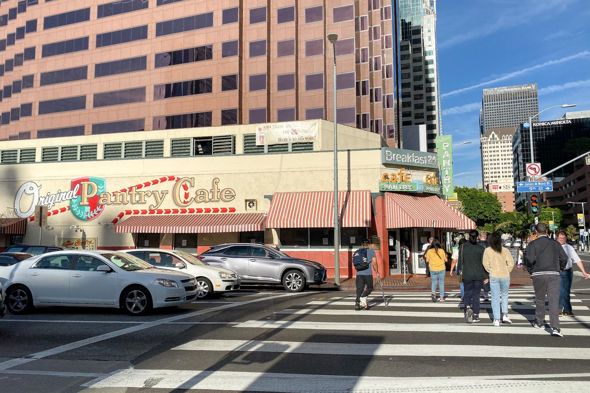 A historic diner cafe sits in front of a crosswalk filled with people.