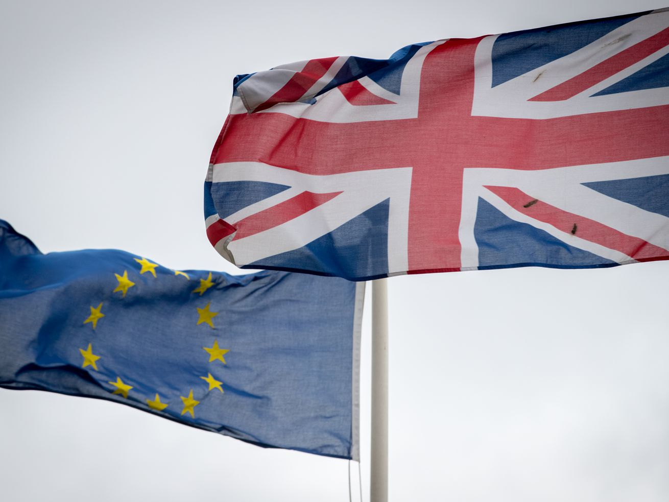 A European Union flag flying beside a United Kingdom flag.
