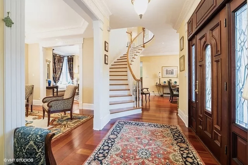 A grand foyer with a large wood door leads to sitting area and a curving staircase leading upward.