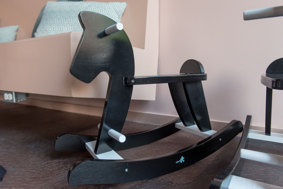 A closeup of a black rocking horse next to a pink booth.